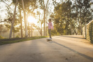 Side view of boy skateboarding on footpath at park during sunset - CAVF50990