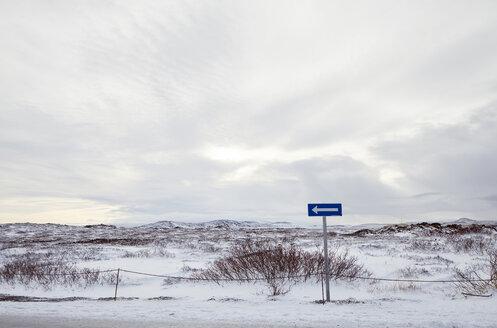 Arrow symbol on snow covered landscape against cloudy sky - CAVF51005