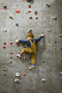 Rear view of boy climbing wall at health club - CAVF51020
