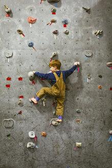 Rear view of boy climbing wall at health club - CAVF51020