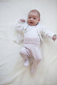 Portrait of baby girl lying on white cloth - JLOF00256