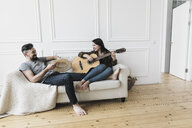 Relaxed couple sitting on couch, woman playing the guitar at home - KMKF00608