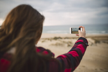 Back view of young woman taking picture with smartphone on the beach - RAEF02185
