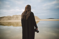 Back view of photographer dressed in black standing on the beach - RAEF02188