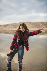 Portrait of laughing young woman  with camera on the beach - RAEF02191