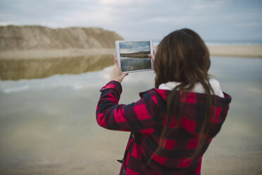 Young woman taking photo with tablet on the beach - RAEF02194