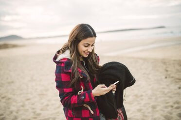 Smiling young woman using smartphone on the beach - RAEF02197