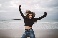 Portrait of happy young woman jumping on the beach - RAEF02200