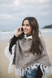 Portrait of smiling young woman on the phone on the beach - RAEF02203