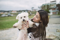 Young woman holding cute white dog - RAEF02206