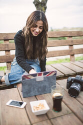 Portrait of smiling young woman sitting on bench outdoors using tablet - RAEF02209