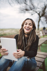 Portrait of laughing young woman sitting on bench outdoors using tablet and earphones - RAEF02212