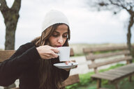 Portrait of young woman drinking cup of coffee outdoors - RAEF02215