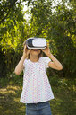 Amazed little girl wearing Virtual Reality Glasses in the garden - LVF07490