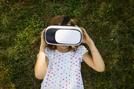 Little girl wearing Virtual Reality Glasses lying on meadow in the garden - LVF07493
