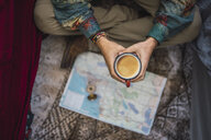 Man drinking coffee over map - KKAF02807
