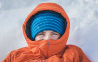 High angle portrait of boy in warm clothing lying on snow covered field - CAVF51055