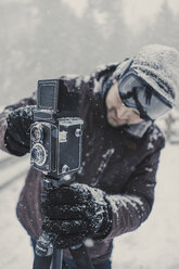 Man photographing while standing in snow covered forest - CAVF51073