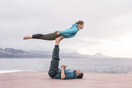 Full length of friends practicing acroyoga on promenade by sea - CAVF51091