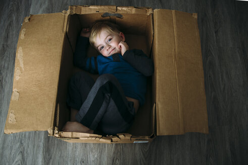 High angle portrait of boy lying in cardboard box at home - CAVF51106