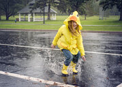Playful girl wearing raincoat while jumping in puddle during rainfall - CAVF51142