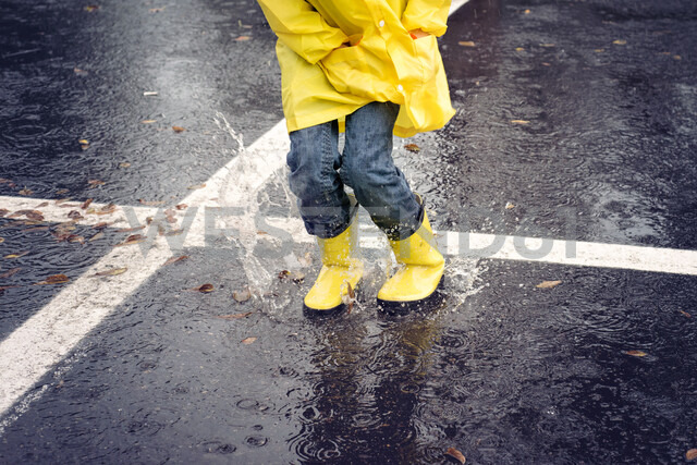 Low section of girl jumping on road during rainfall - CAVF51145 - Cavan Images/Westend61