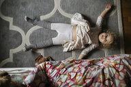 Overhead portrait of girl lying on carpet in bedroom - CAVF51154