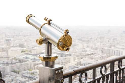 Coin-operated binocular on railing by cityscape against clear sky - CAVF51164