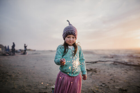 Girl wearing knit hat while holding illuminated sparkler against sky at beach - CAVF51176