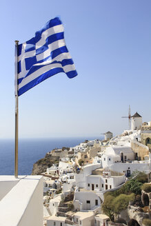 Greek Flag waving by sea against town and clear sky - CAVF51203