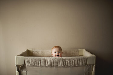 Portrait of baby boy in crib against wall at home - CAVF51245