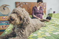 Pregnant woman reading book with poodle sitting on bed at home - CAVF51272