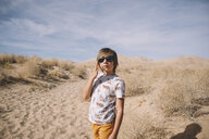 Boy wearing sunglasses while standing at desert during sunny day - CAVF51290