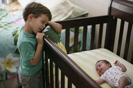 High angle view of brother looking at sister lying in crib at home - CAVF51320