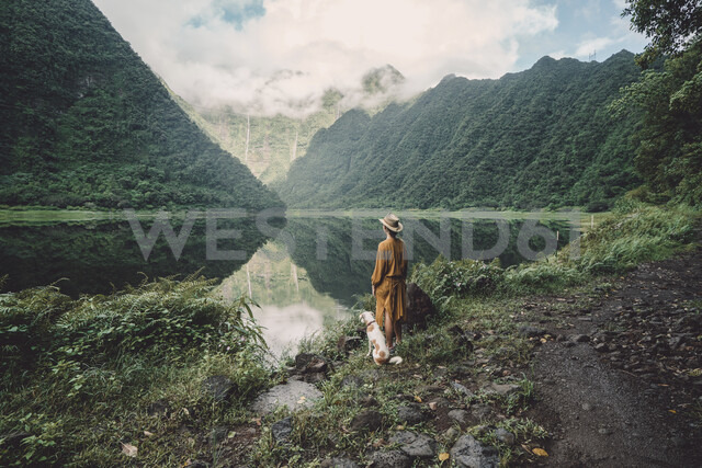 Rear view of woman with dog standing at lakeshore against cloudy sky in forest - CAVF51344