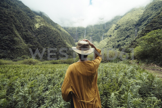 Rear view of woman wearing hat standing against cloudy sky in forest - CAVF51347