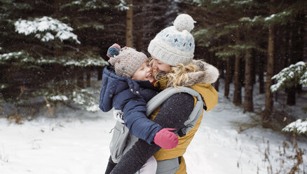Cheerful mother carrying daughter in forest during winter - CAVF51359