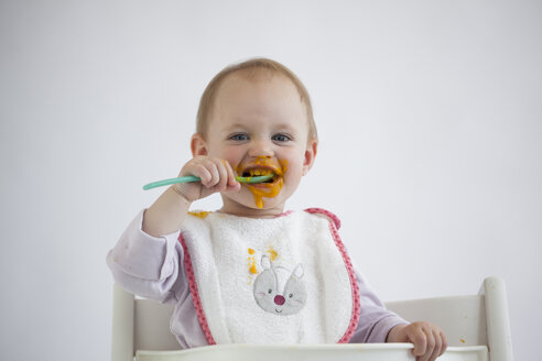 Portrait of smeared baby girl on high chair eating mush - JLOF00286