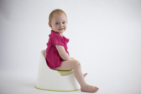 Portrait of smiling baby girl sitting on potty - JLOF00292
