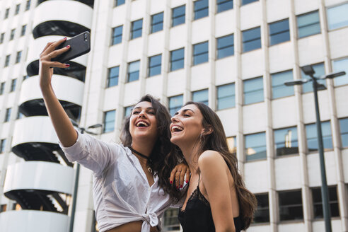 Laughing friends taking selfie with cell phone - KKAF02821