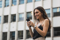 Smiling young woman using cell phone - KKAF02824