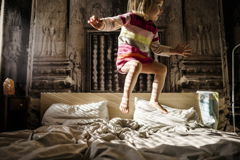 Little girl jumping on parent's bed at home - PSIF00129