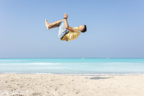 Young man doing a somersault on the beach - WPEF00979