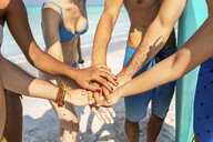 Group of friends on the beach stacking hands - WPEF01003