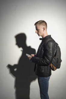 Young man with backpack wearing black leather jacket looking at cell phone - VGF00077
