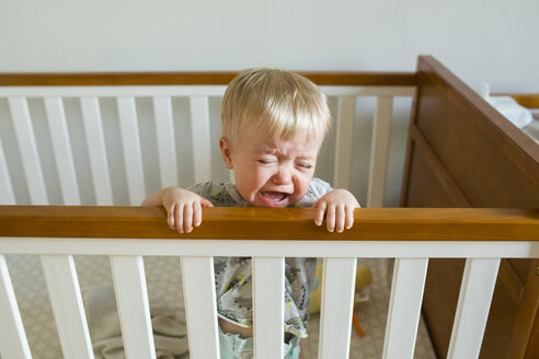 Baby boy crying while standing in crib at home - CAVF51365
