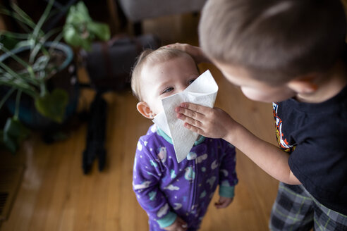 Bother wiping sister's face with facial tissue at home - CAVF51377