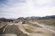 Mid distance view of hiker amidst desert against cloudy sky at Death Valley National Park - CAVF51383