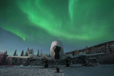 Snow covered airplane against aurora borealis - CAVF51395