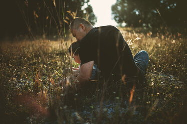 Rear view of father with son sitting on grassy field - CAVF51434